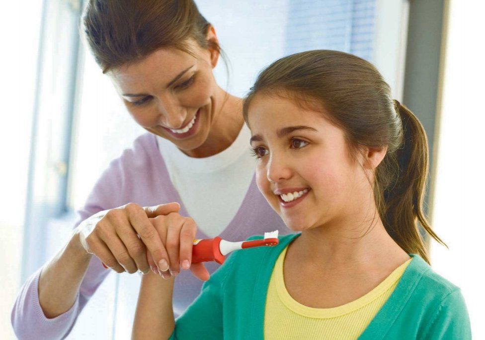 Girl brushing teeth with mum's help